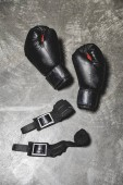 Fotografie top view of boxing gloves with wrist wraps lying on concrete surface