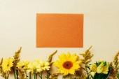 plochý ležela s krásnými květinami a prázdné oranžová karta uspořádání na béžové pozadí