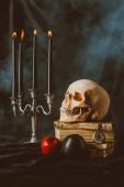 Svícen, halloween lebka, starých knih s černým a červeným jablka na černou látkou s kouřem