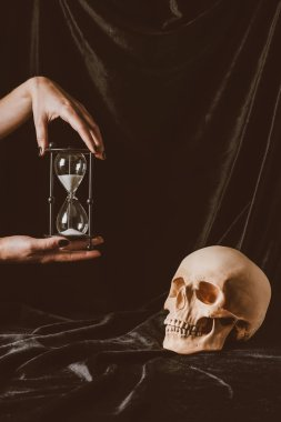 cropped view of woman holding sand clock near skull on black cloth