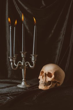 Creepy skull and candelabrum with black candles on dark cloth for halloween stock vector