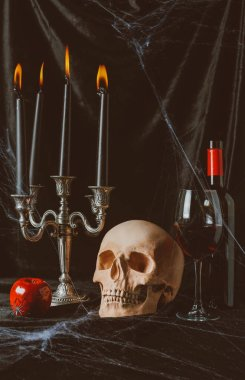 halloween skull, apple, red wine and candelabrum with candles on black cloth with spider web