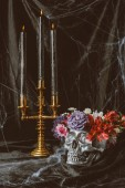 Fotografie silver skull with flowers and candelabrum with candles on black cloth with spider web for halloween