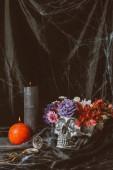 Fotografie stříbrná lebka halloween s květinami, vintage hodiny a svíčky na černou látkou s pavučina