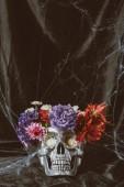 Fotografia teschio argento di halloween con i fiori sul panno scuro con ragnatela