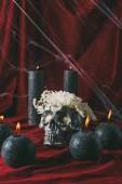 Fotografia teschio halloween argento con fiori e candele nere sul panno rosso con ragnatela