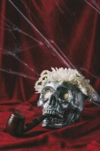Photo silver skull with flowers and smoking pipe on red cloth with spider web