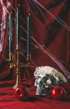 apples, silver skull with flowers and candelabrum with candles on red cloth with spider web