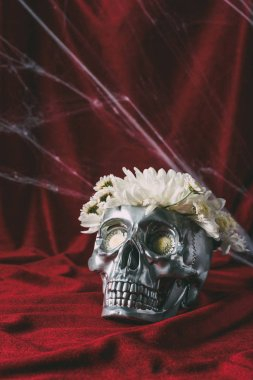 halloween silver skull with flowers on red cloth with spider web