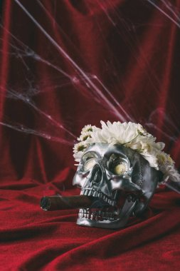 silver skull with flowers smoking cigar on red cloth with spider web