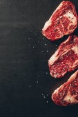 Blick von oben auf rohe Fleischsteaks und Gewürze in der Küche