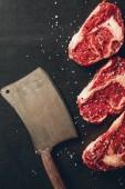 Blick von oben auf rohe Fleischsteaks und Spaltpilze in der Küche