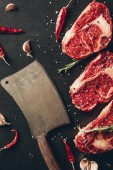 top view of raw meat steaks, spices and cleaver on surface in kitchen