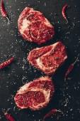 pohled shora syrové steaky a rozptýlené koření na stole v kuchyni