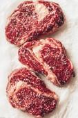 pohled shora ze tří kusů syrové maso steaky solí na papír na pečení v kuchyni