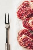 pohled ze tří kusů syrové maso steaky a vidlička na stole v kuchyni