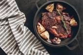 pohled shora vařené steak s citrony a bobule na pánev, ubrus na povrchu v kuchyni