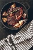 pohled z vařené steak s citrony a bobule na pánev, pruhovaný ubrus na povrchu v kuchyni