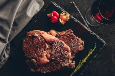 elevated view of roasted steaks on cutting boards, glass of red wine on tabletop in kitchen