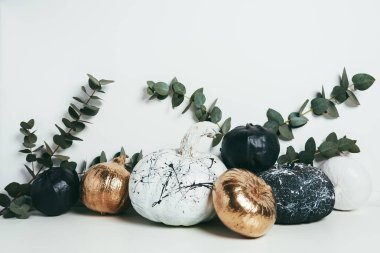 still life with golden, black and white painted pumpkins with eucalyptus branches, halloween decoration