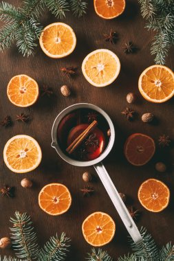 top view of mulled wine with fresh oranges and spices on wooden background with pine branches