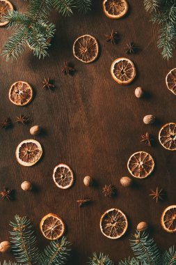 top view of dried orange slices, anise stars and nutmeg seeds on wooden background with pine branches for christmas