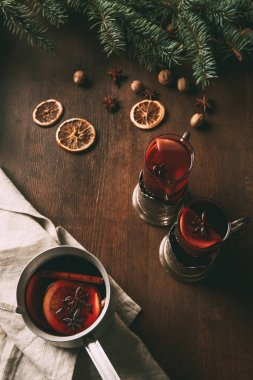 mulled wine in saucepan and glass cups on wooden background with dried orange slices and spices