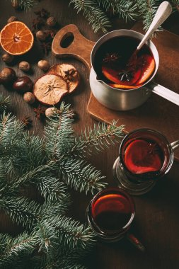 hot mulled wine in saucepan and glass cups with spices on wooden background with fir branches