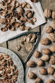 Fotografie top view of whole and cracked walnuts, nutcracker, vintage plate, cloth and newspaper on wooden table