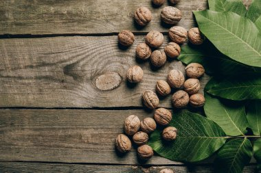 top view of whole natural walnuts and green leaves on wooden table