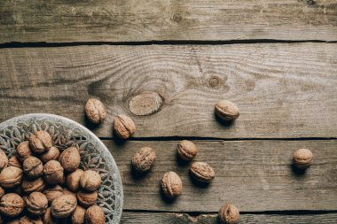 Top view of ripe organic walnuts and plate on wooden table stock vector
