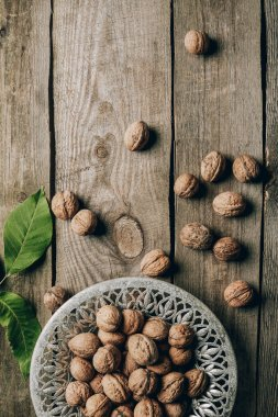 top view of ripe organic walnuts, green leaves and plate on wooden table