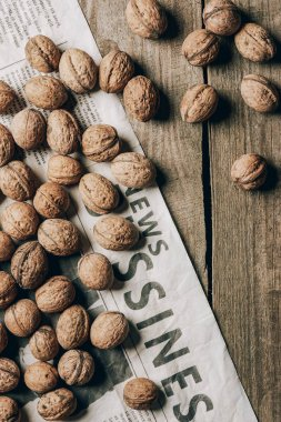 top view of whole walnuts and business newspaper on wooden table
