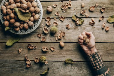 cropped shot of person holding raw ripe walnuts above wooden table