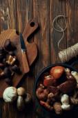 Fotografia vista superiore di funghi crudi freschi, tagliere, coltello, pan e corda sulla tavola di legno