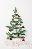 top view of green pine branch decorated as festive christmas tree with glitters on white background