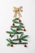 pohled shora zelené borové větve zdobené jako slavnostní vánoční strom s lukem na bílém pozadí