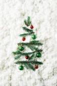 pohled shora zelené borové větve s vánoční plesy v slavnostní vánoční stromeček na pozadí bílé vaty