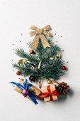 top view of green pine branch decorated as festive christmas tree with gifts and bow on white background