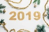 vista superiore del segno anno 2019, rami di pino, ghirlande dorate e sfere di Natale su priorità bassa bianca