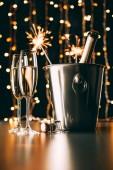 pezsgő-party ragyog a garland világos háttér, karácsonyi concept