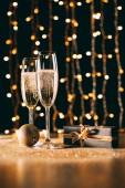 sklenic šampaňského, dar a cetka na věnec světlé pozadí, vánoční koncepce