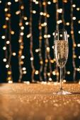 hladinou jednu sklenku šampaňského na věnec světlé pozadí, vánoční koncepce