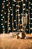 Sklenka šampaňského, zlaté ozdoby a současnost na věnec světlé pozadí, vánoční koncepce