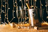 zwei Gläser und Sektflasche im Eimer auf hellem Girlanden-Hintergrund, Weihnachtskonzept
