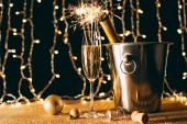 Champagnerflasche im Eimer, Glas mit Weihnachtsfunkeln auf Lichterkranz Hintergrund