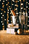 úrovně hladiny dárků, sklenice šampaňského a ozdoby na věnec světlé pozadí, vánoční koncepce