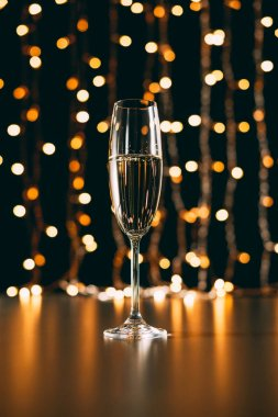 one glass of champagne on garland light background, christmas concept