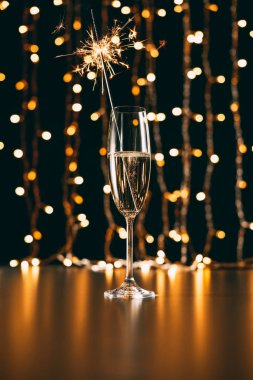 champagne with christmas sparkle on garland light background