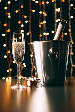 champagne bottle in bucket and glass on garland light background, christmas concept